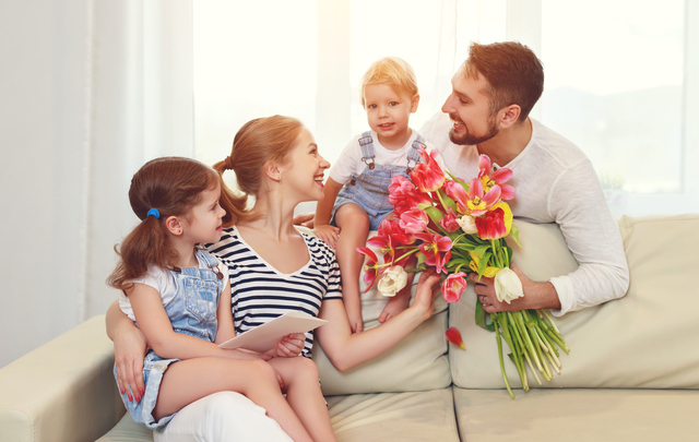 母親に花束を渡す父親