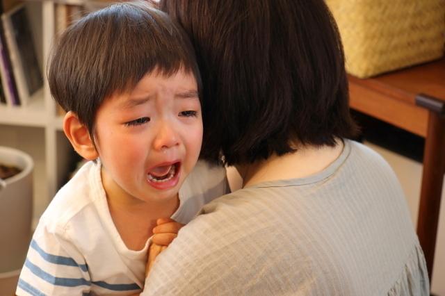 泣く子どもを抱きしめる