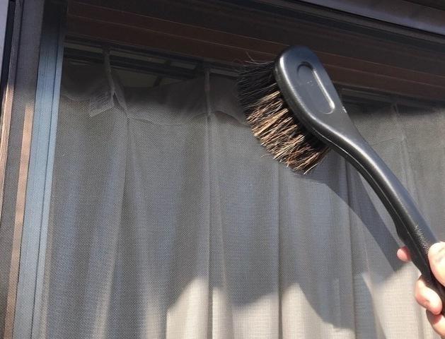 網戸をブラシで掃く