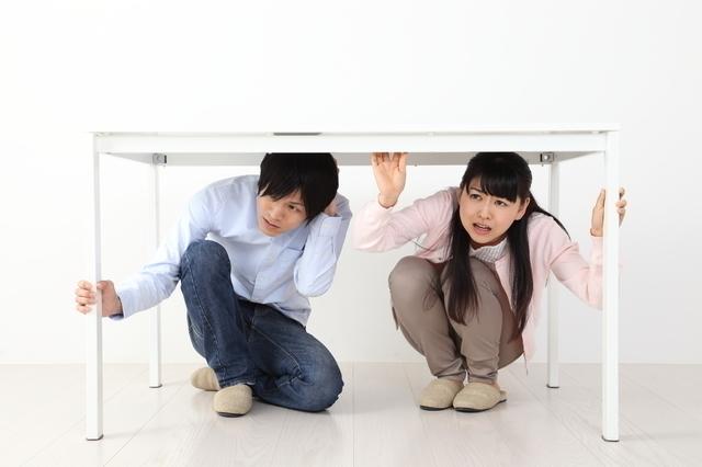 机の下に避難する男女