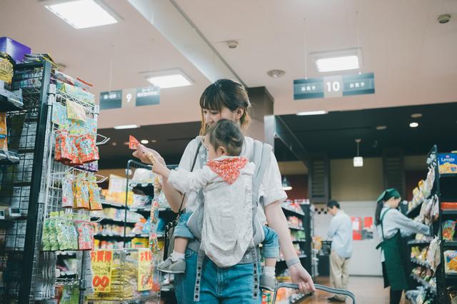 スーパーで商品を選ぶ主婦