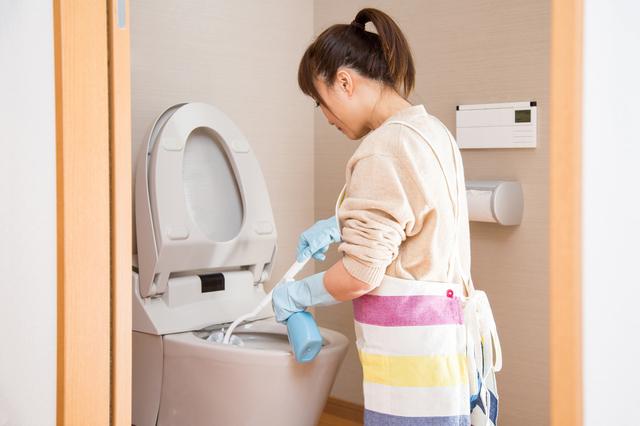 トイレ掃除をする女性