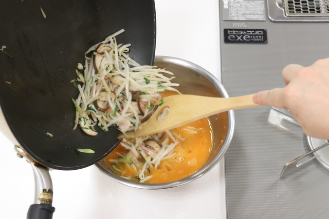 炒めた野菜を玉子にくわえる