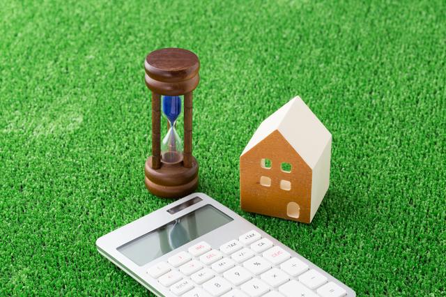 家の模型と砂時計と電卓