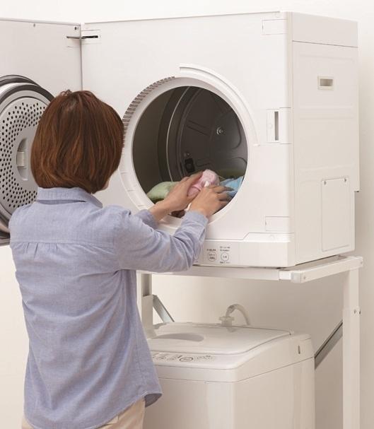乾燥機に洗濯物をいれる女性