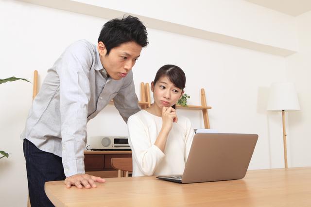 PCを見ながら悩む女性と男性