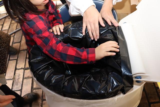 便座をおろして、その上から携帯簡易トイレの汚物袋をかぶせる