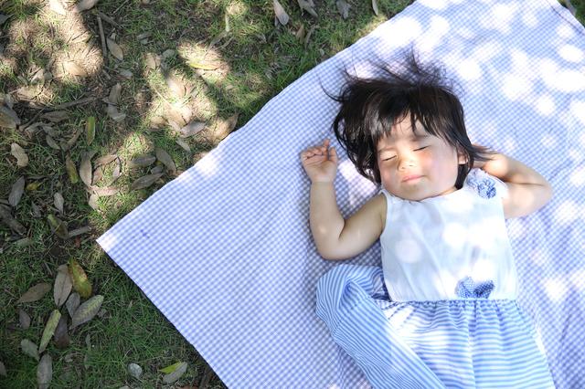 屋外で昼寝する子ども