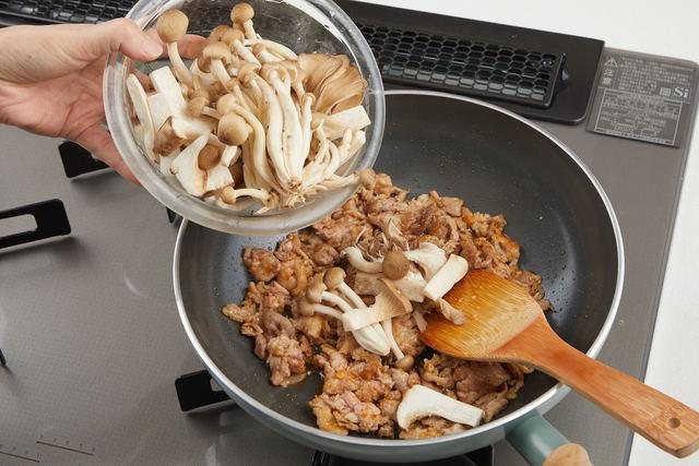 炒めた肉にキノコを加える