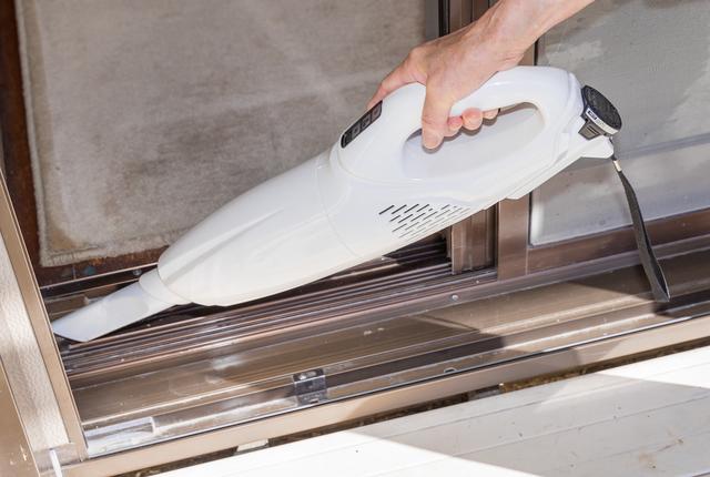 窓枠のホコリを掃除機で吸い取るところ