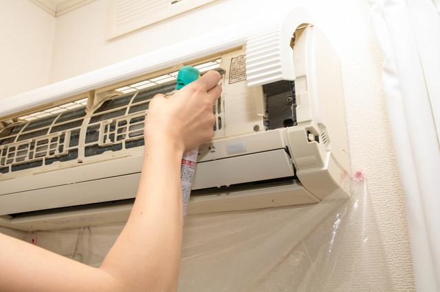 エアコンにファン専用の掃除スプレーをかけるところ