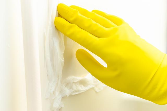 カビ取り専用洗剤をかけたお風呂の壁にキッチンペーパーでパックをしているところ