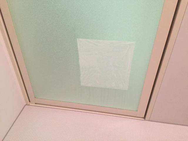 クエン酸スプレーとキッチンペーパーで風呂のドアを掃除するところ
