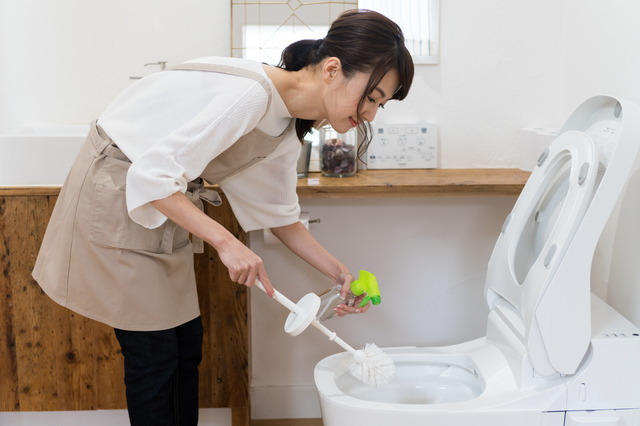 トイレ掃除している女性