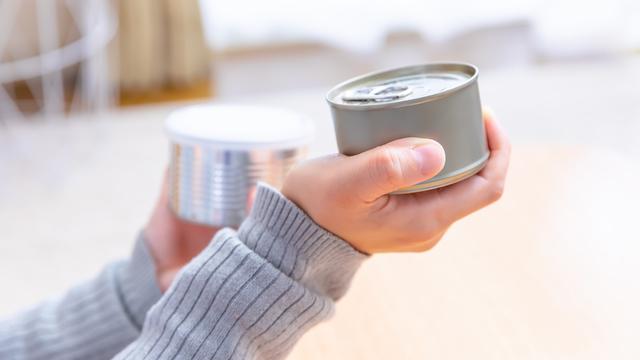 缶詰を確認する女性の手元