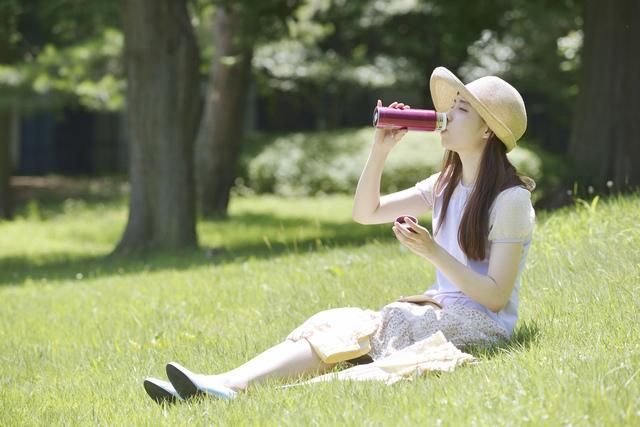 水筒から飲み物を飲む女性