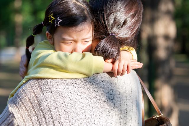 親に抱きかかえられている子どもの様子