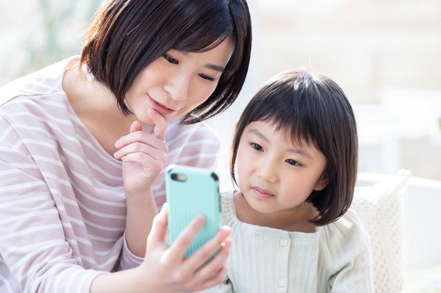大人と子どもが一緒にスマホの画面を見ている様子