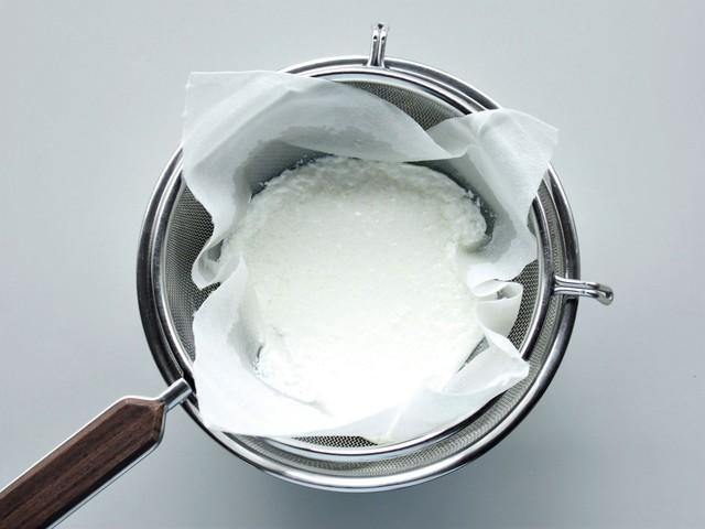 キッチンペーパーを2枚重ねたザルに鍋の中身を注ぐ様子
