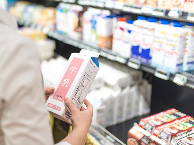 スーパーで売られている牛乳を手に取る様子