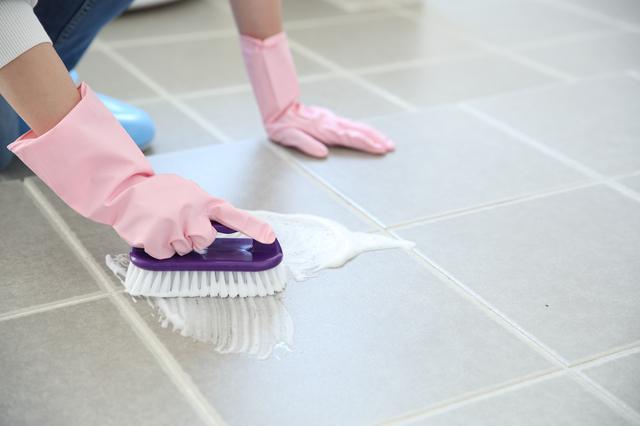 浴室の床を掃除する女性