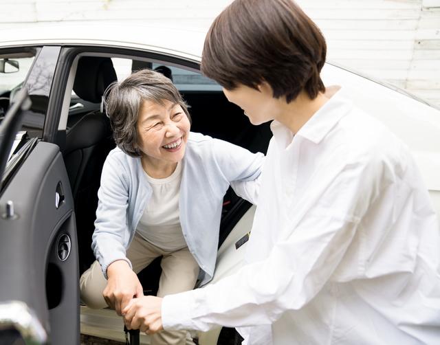 母親の手を取り支える女性