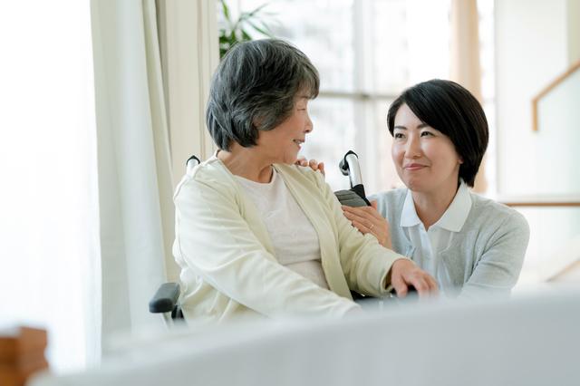 車いすに座る母親をサポートする女性の様子