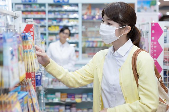 薬局で商品を探すマスクの女性