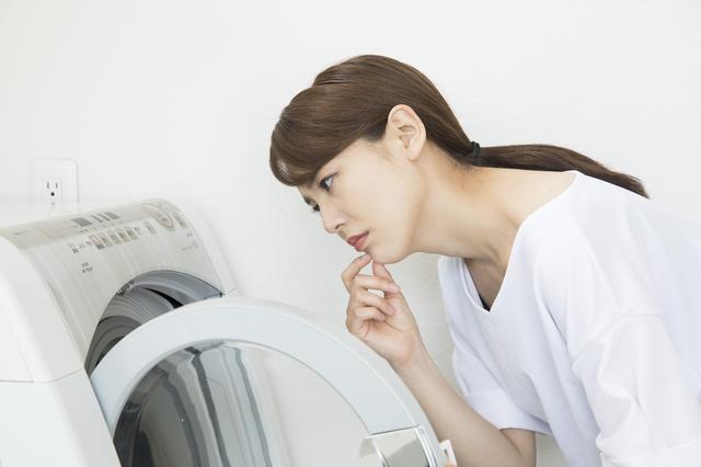 洗濯機を覗き込む人