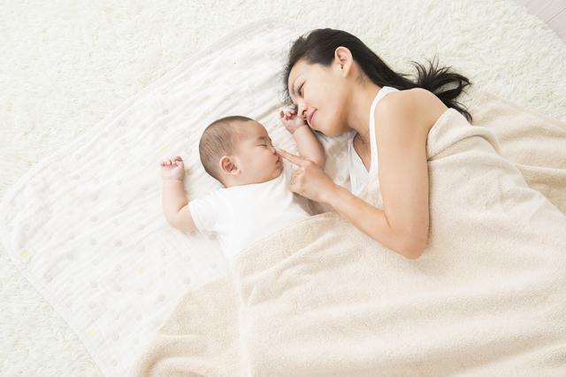 赤ちゃんと添い寝する女性