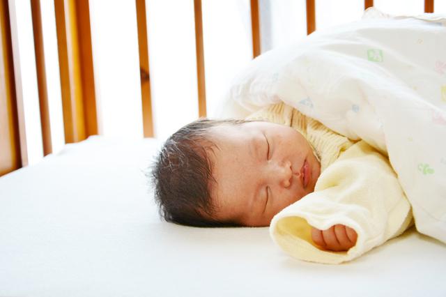ベビーベッドで眠る赤ちゃん