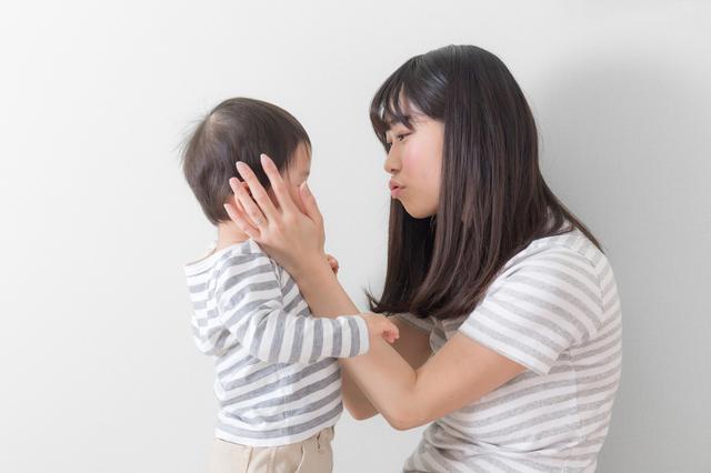 子どもの顔を包む女性
