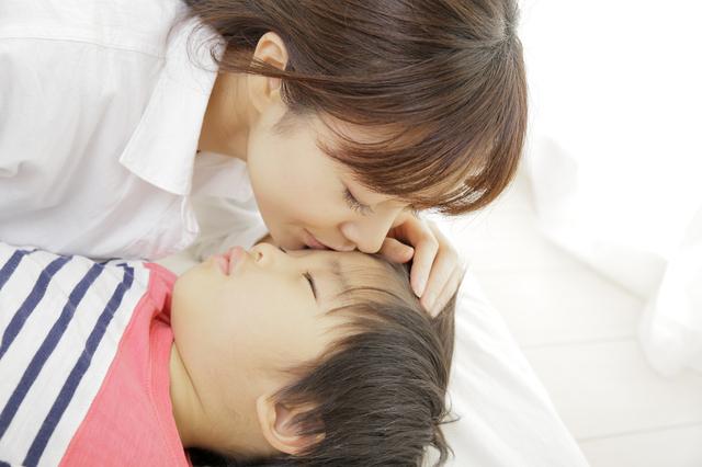 子どもの額にキスする母親