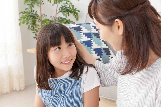 子どもの頭を撫でる女性