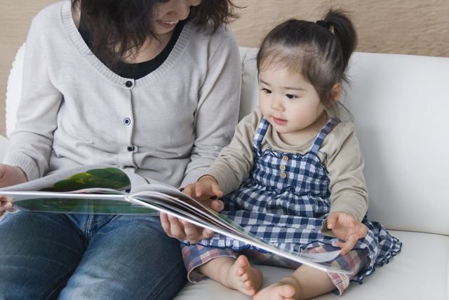 母親と一緒に絵本を読む子ども