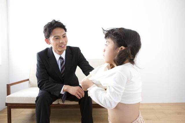 子どもの着替えを見守る男性