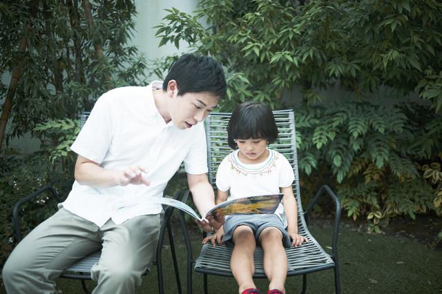 屋外で絵本の読み聞かせをする父子