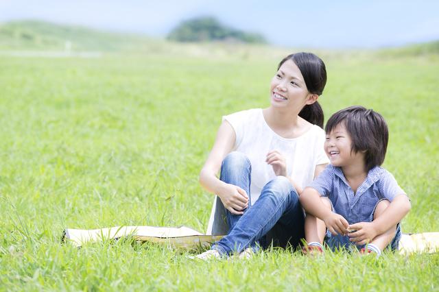 草むらに座る親子
