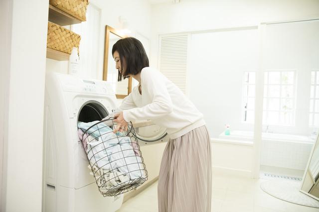洗濯物を洗濯機に入れる