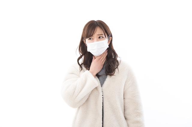 喉を押さえるマスクの女性